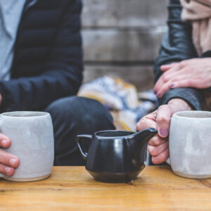 People holding a nice cup of coffee while having a conversation